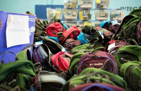 Donated backpacks and supplies were piled in the school's gym.